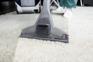 cropped shot of person cleaning white carpet with professional vacuum cleaner